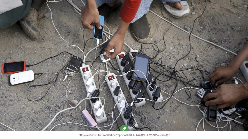 closeup of several people charging their smartphones